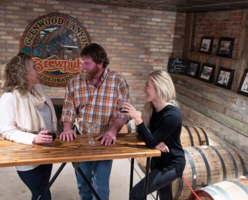 Friends chatting in Glenwood Canyon Brewpub barrel room