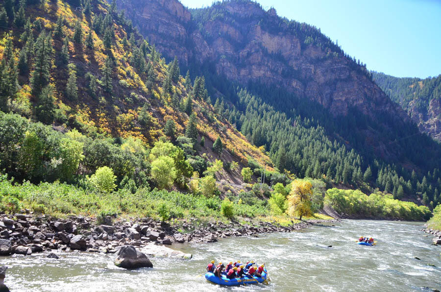 one rafting boat on colorado river with sourrounded by fall foliage in Glenwood Canyon