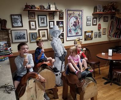 children sitting on saddles inside of the store