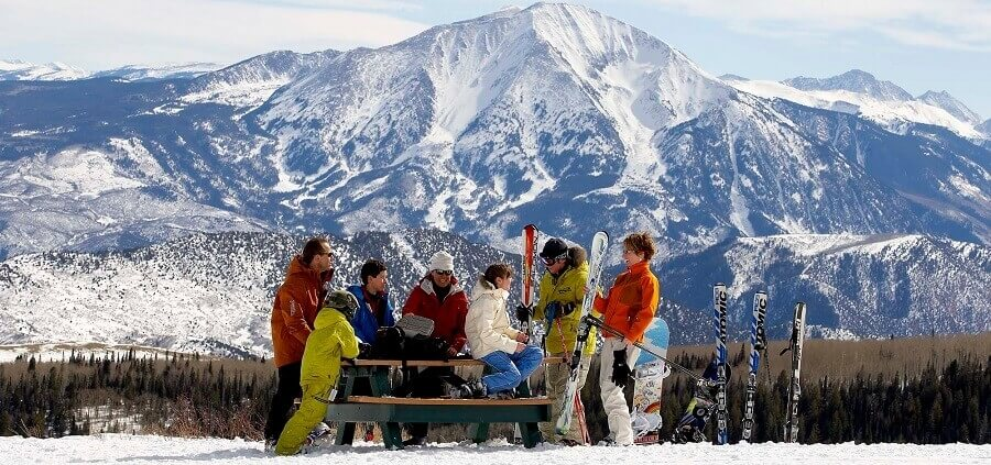 group of people/skiers sitting on bench, mount sopris in the background