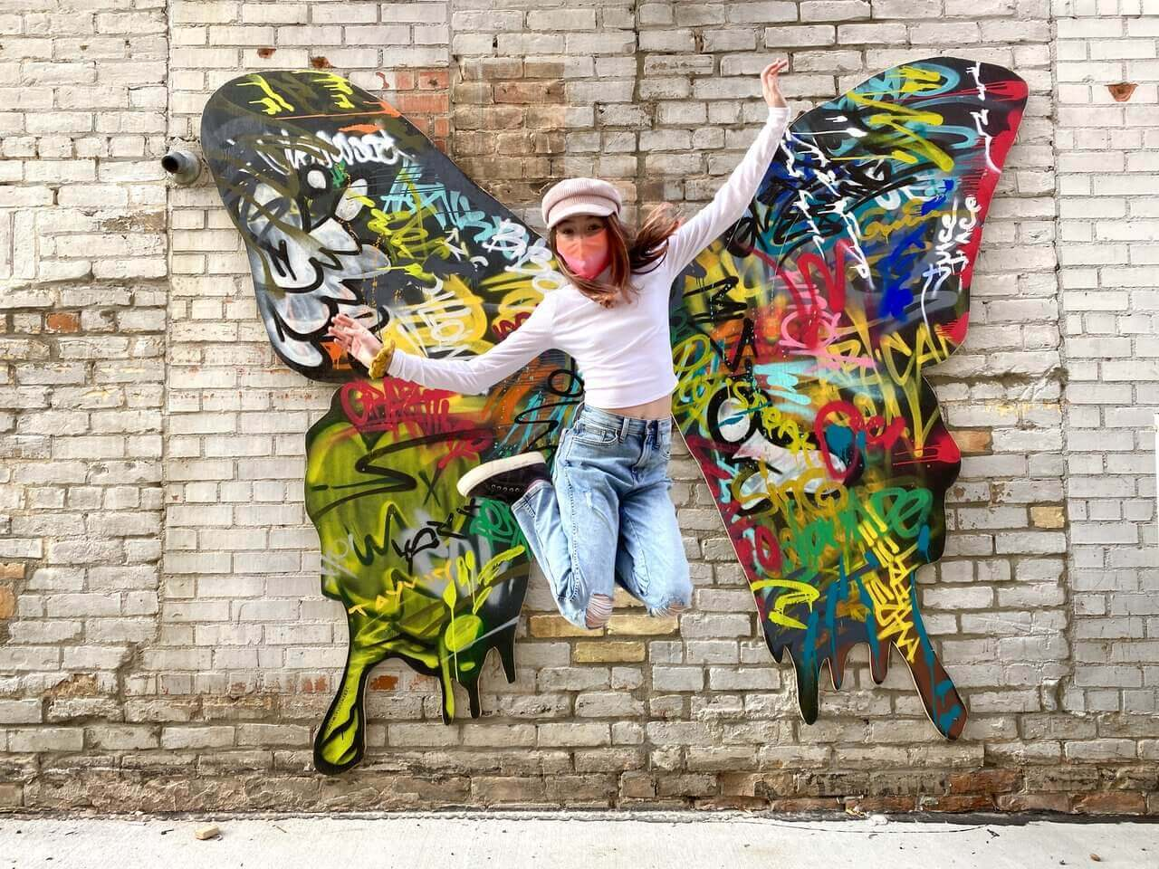 girl jumping in front of wing art wearing mask